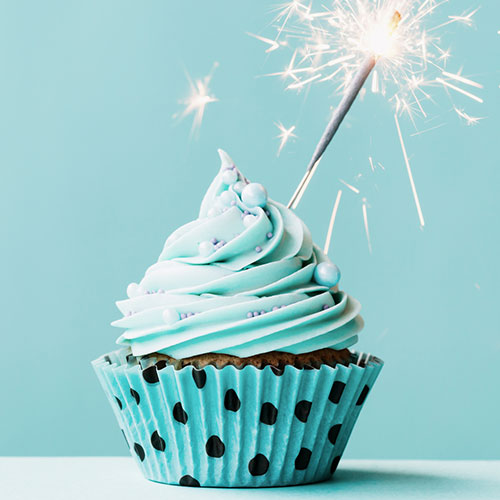 A chocolate cupcake with blue frosting in a polka-dot wrapper with a sparkler.